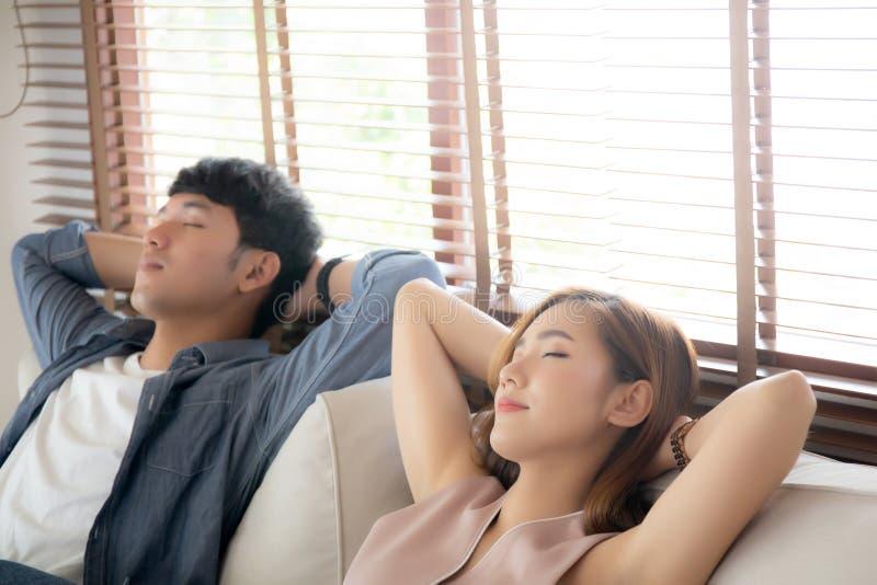 Det unga asiatiska parleendet kopplar av bekvämt på soffan i vardagsrummet, i ferie, familjfritid och att vila med lyckligt arkivfoton