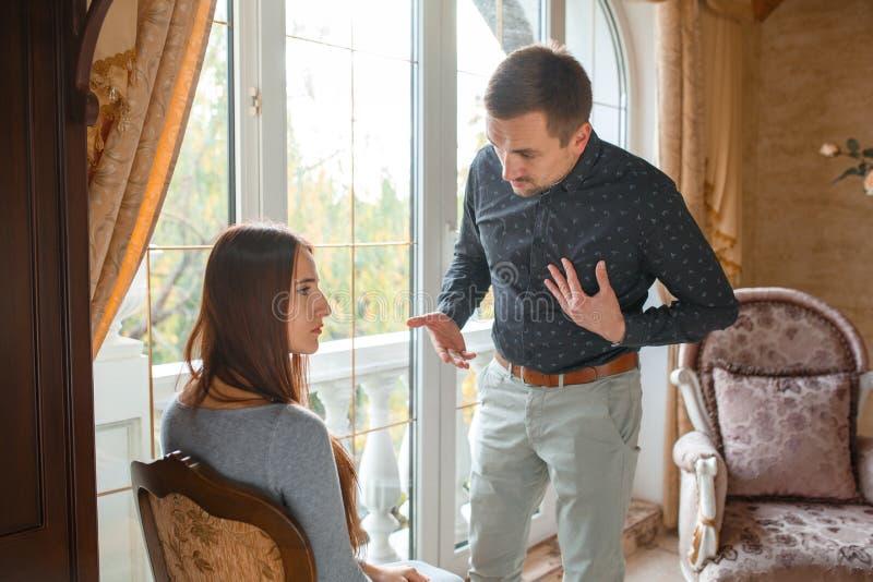 Det unga gifta paret grälar på fönstret fotografering för bildbyråer