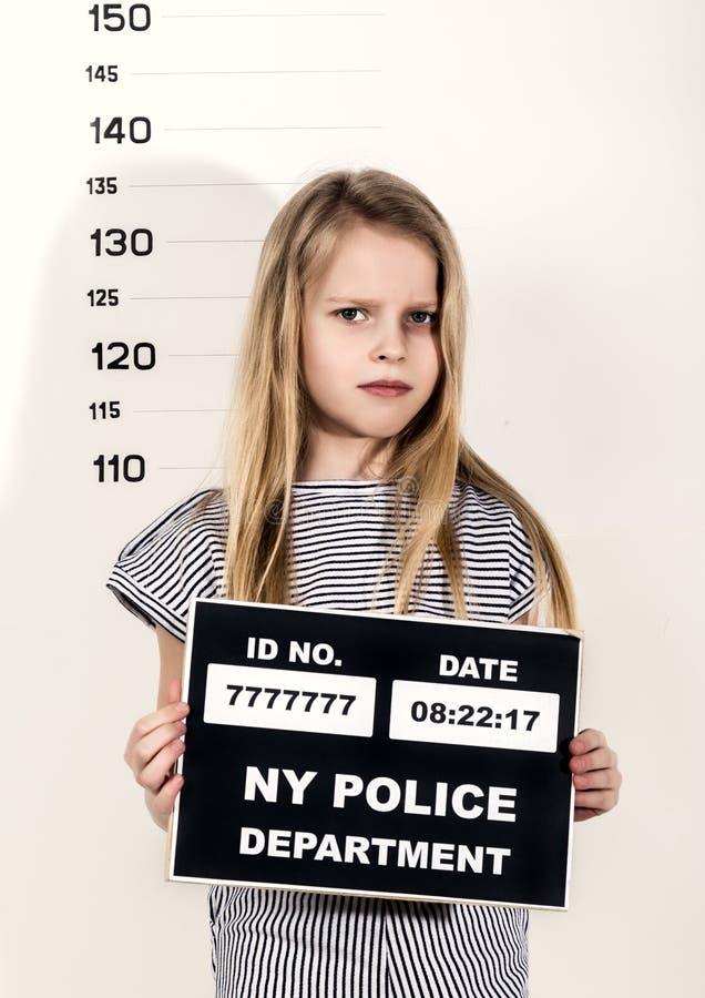 Det unga härliga blonda barnet med ett tecken som är brottsligt rånar skott svåra barn, social spänning arkivfoto