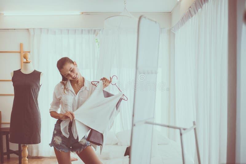 Det unga härliga kvinnaanseendet i kläder shoppar och välja klänningar, lyckligt och att le, mode- och livsstilbegrepp arkivbilder