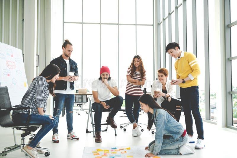 Det unga idérika olika gruppmötet och att se projektplanet som är lekmanna- ut på golv, diskuterar eller kläckning av ideeraffärs royaltyfria foton