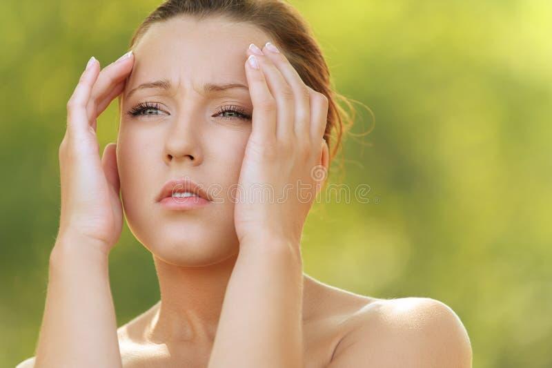 Det unga kvinnaholdinghuvudet smärtar in royaltyfri foto