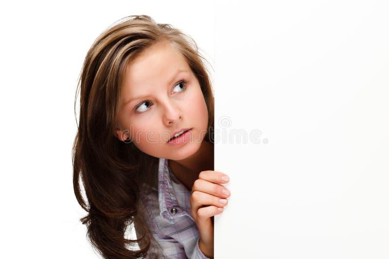 Den unga attraktiva kvinnan bak tomt stiger ombord på vitbakgrund fotografering för bildbyråer