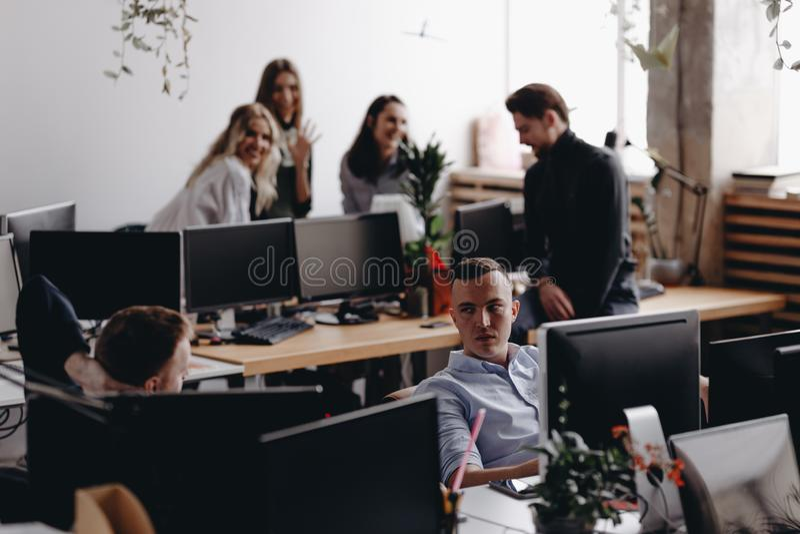 Det unga laget av kollegor diskuterar projektet i ett stilfullt modernt kontor Arbetsprocess i kontoret royaltyfria bilder