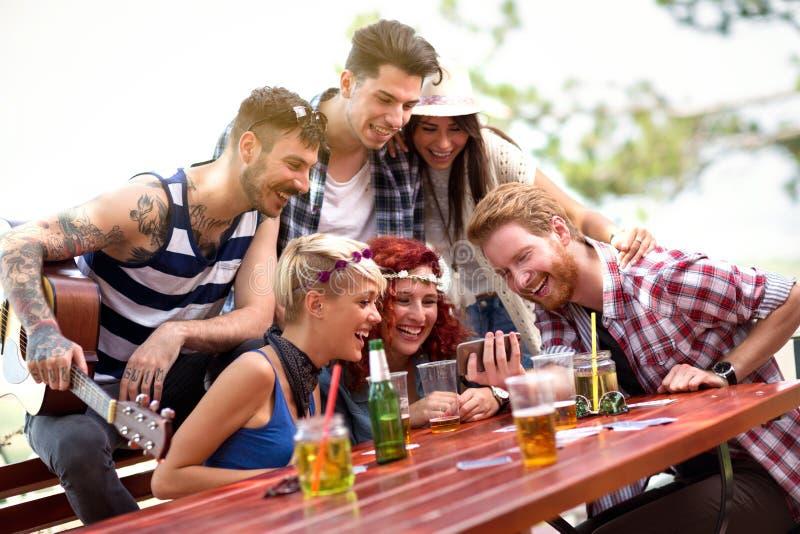 Det unga laget skrattar, medan hålla ögonen på deras foto på mobiltelefonen fotografering för bildbyråer