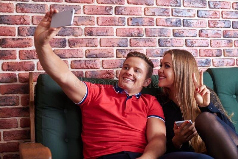 Det unga lycklig-seende paret är att le som är älskvärt, medan ta selfie royaltyfri fotografi