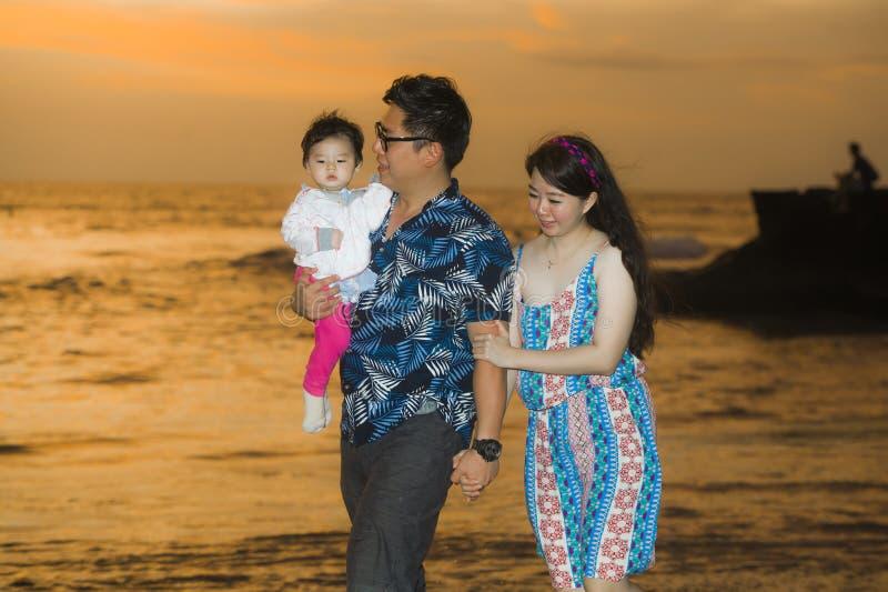 Det unga lyckliga och härliga asiatiska koreanska parinnehavet behandla som ett barn flickadottern som går på solnedgångstranden  royaltyfria bilder