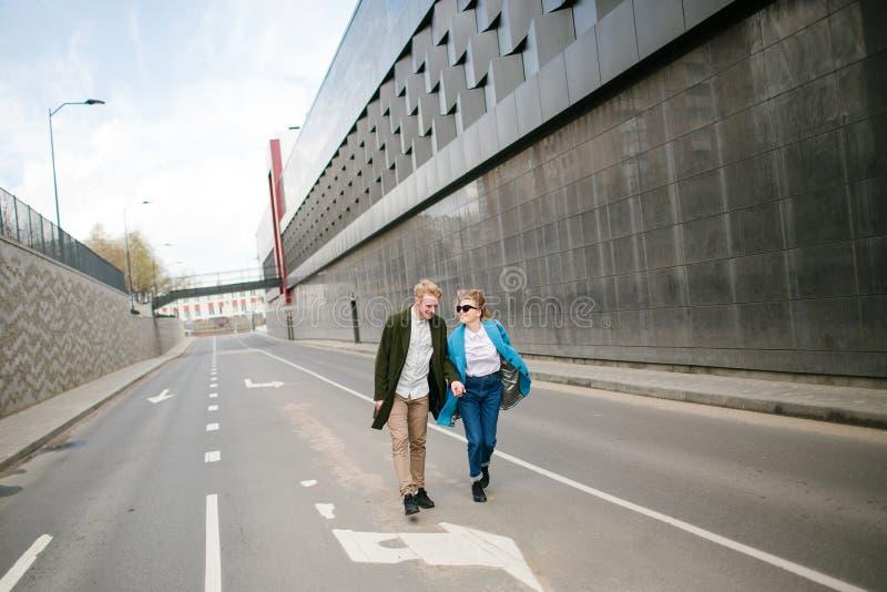 Det unga lyckliga paret som går stadsgatainnehavet, räcker förälskat arkivfoto