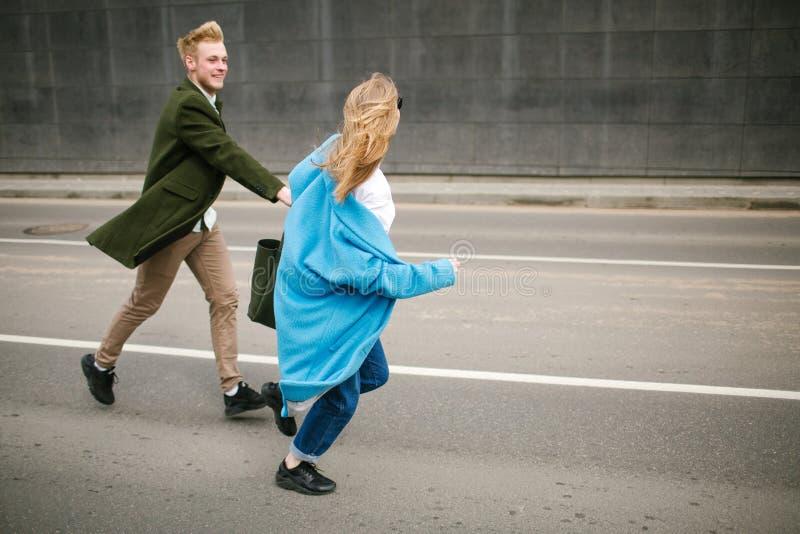 Det unga lyckliga paret som går stadsgatainnehavet, räcker förälskat royaltyfria bilder