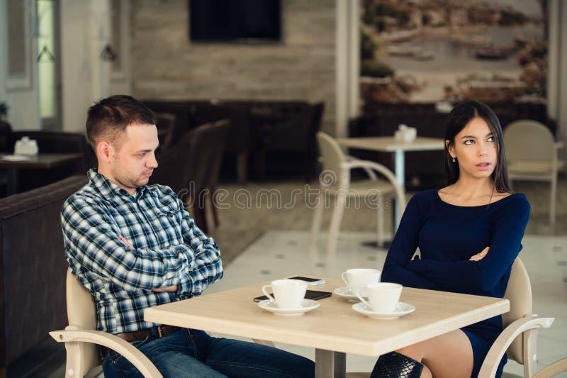 Det unga olyckliga gifta paret som har allvarligt, grälar på kafét royaltyfri bild