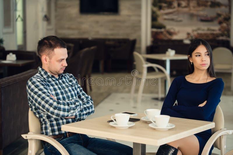 Det unga olyckliga gifta paret som har allvarligt, grälar på kafét arkivfoto