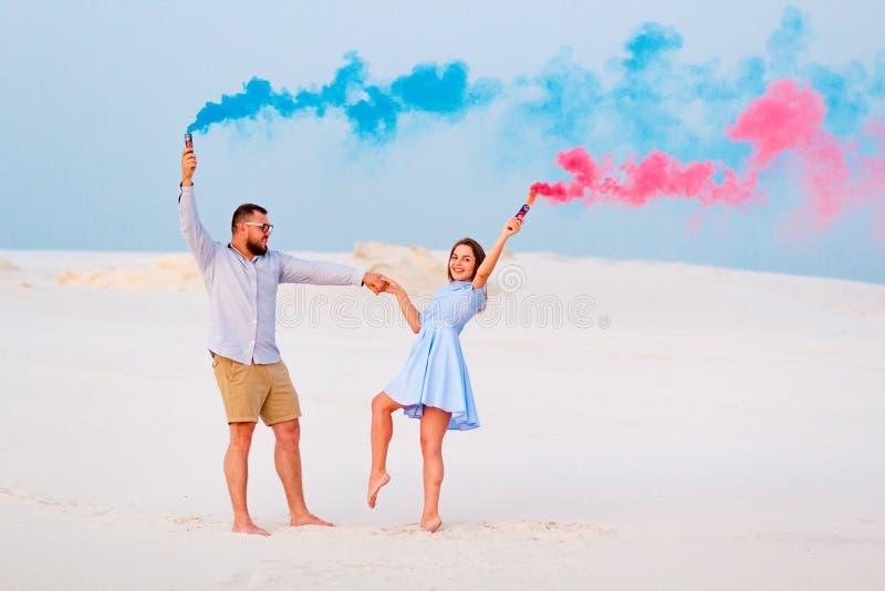 Det unga paranseendet på en sand och att rymma kulör rök bombarderar, romantiska par med blå färg, och rök för röd färg bombarder arkivbilder
