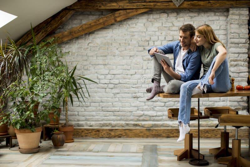 Det unga paret använder en digital minnestavla och ler i kök hemma royaltyfri foto