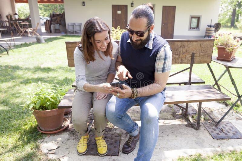 Det unga paret av vänner konsulterar den utomhus- smarta telefonen royaltyfri foto