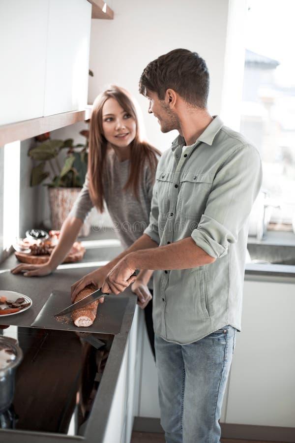 Det unga paret förbereder frukosten i deras kök royaltyfri bild