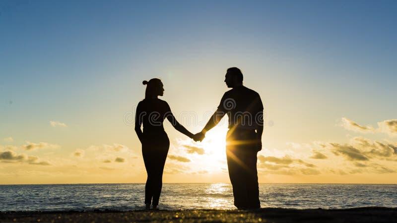 Det unga paret går i vattnet på sommarstranden över havssolnedgång Två konturer mot solen bara gift arkivfoto
