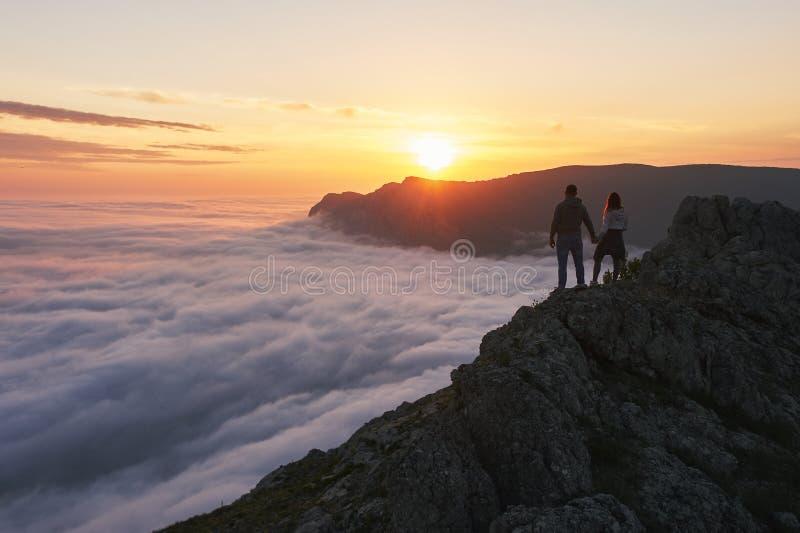 Det unga paret st?r i bergen ovanf?r molnen och blickarna p? den h?rliga solnedg?ngsikten arkivfoton