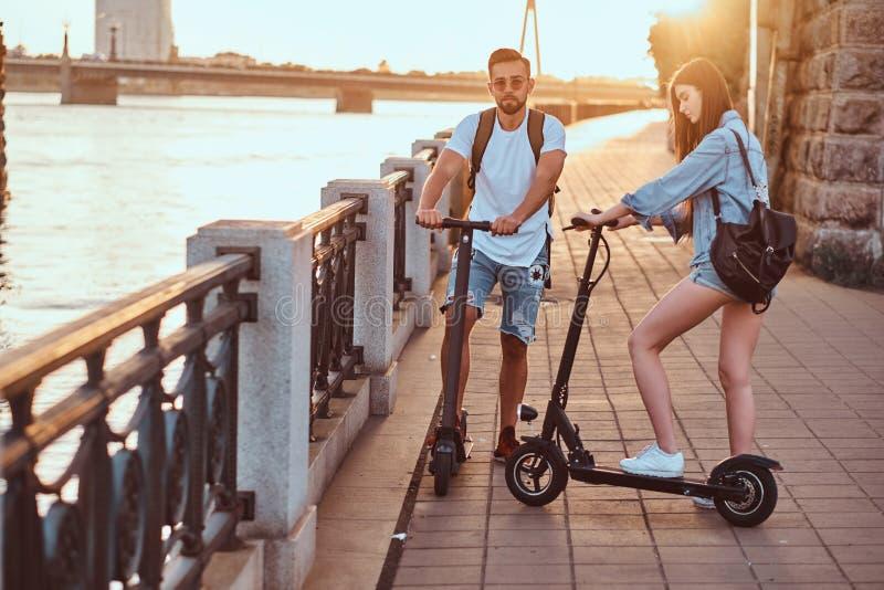Det unga paret tycker om den electro sparkcykelns ridning royaltyfri fotografi