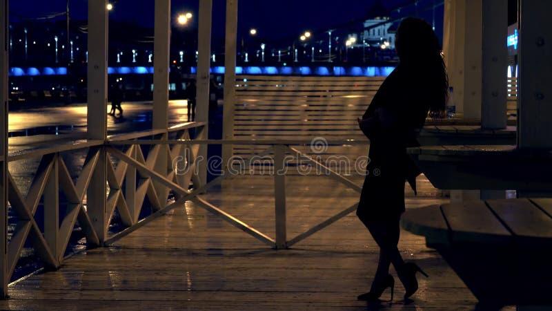 Det unga romantiska kvinnaanseendet på terrassen i Moskva parkerar på natten royaltyfria foton