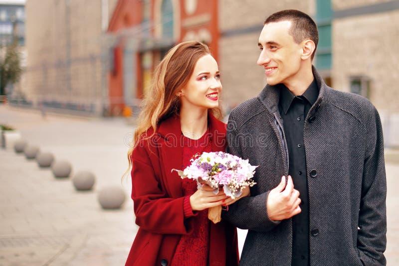 Det unga romantiska paret, den härliga flickan med blommor har datummärkning i staden Man i grå överrock och modell i rött lag arkivbilder