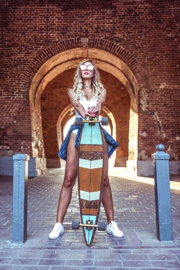 Det unga stilfulla och härliga flickaanseendet, i sommar i staden, bakgrunden är en tegelstenbåge Skateboard longboard royaltyfri fotografi