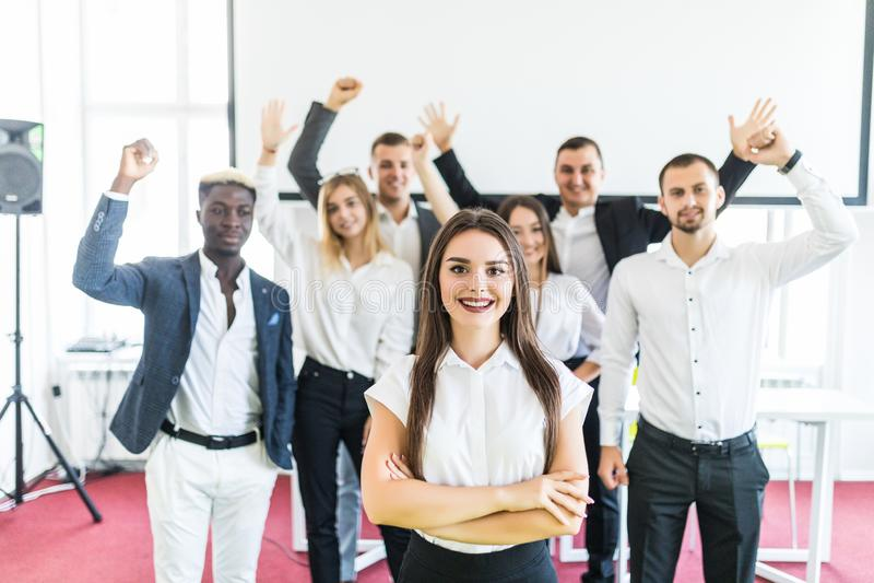 Det unga vita kvinnliga utövande anseendet med korsade händer av kollegor med deras armar som lyfts upp, firar framme seger fotografering för bildbyråer