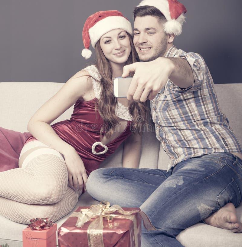 Det unga vuxna paret tar en selfie på soffan på jultid royaltyfri foto