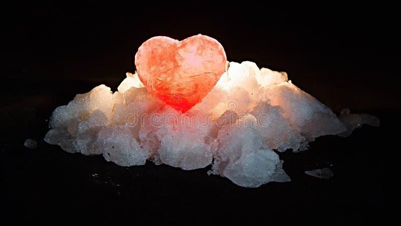 Det upplysta behind för röd ishjärta på en kulle av vit snö royaltyfri fotografi