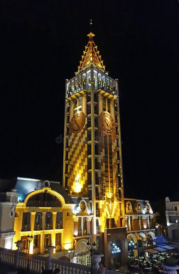 Det upplysta klockatornet med den guld- tornspiran stiger över gatan av den gamla staden, Batumi, Georgia royaltyfri fotografi