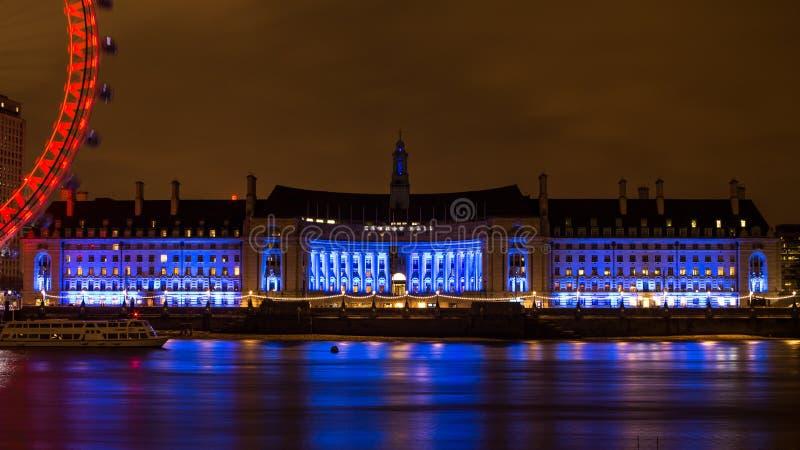 Det upplysta Southbank stadshuset reflekterar på ett mjuka Thames River royaltyfri foto