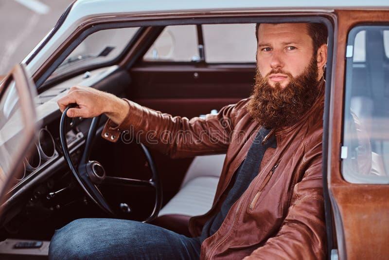 Det uppsökte manliga iklädda bruntläderomslaget sitter bak hjulet av en stämd retro bil med den öppna dörren arkivfoton