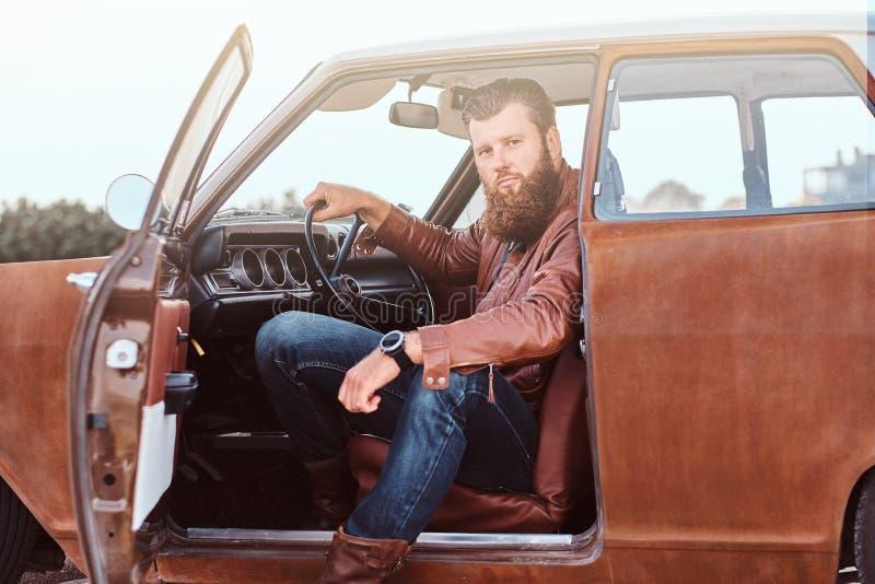 Det uppsökte manliga iklädda bruntläderomslaget sitter bak hjulet av en stämd retro bil med den öppna dörren arkivfoto