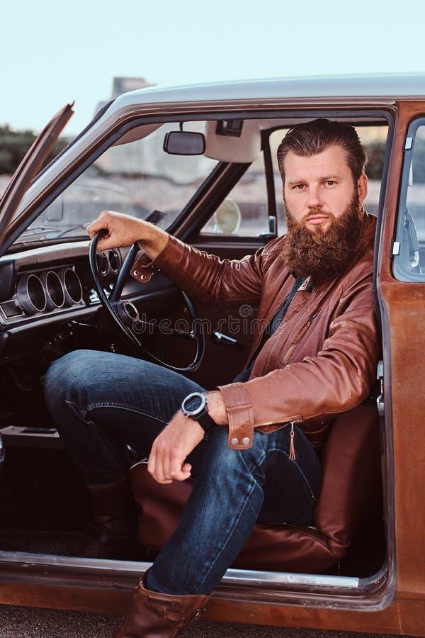 Det uppsökte manliga iklädda bruntläderomslaget sitter bak hjulet av en stämd retro bil med den öppna dörren royaltyfri fotografi