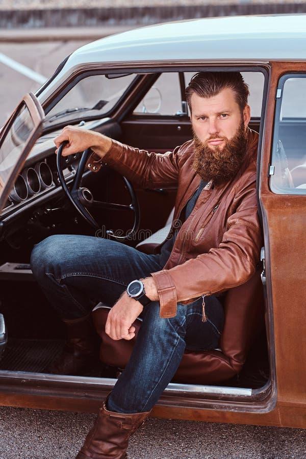 Det uppsökte manliga iklädda bruntläderomslaget sitter bak hjulet av en stämd retro bil med den öppna dörren arkivbild