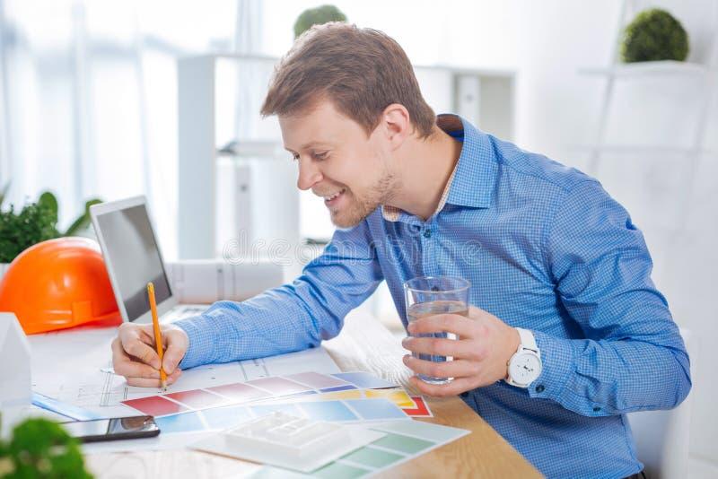 Det upptagna barnet iscensätter att le medan dricksvatten på arbete arkivfoton