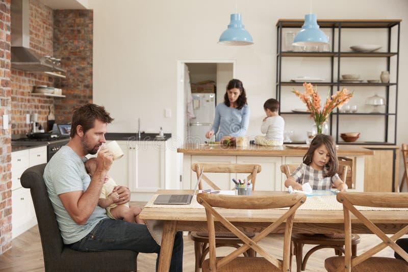 Det upptagna familjhemmet med fadern Working As Mother förbereder mål arkivfoton
