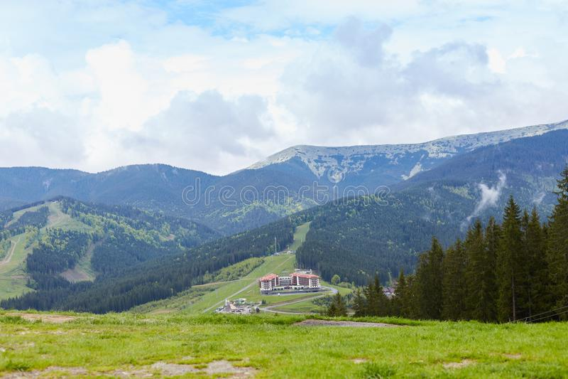 Det utomhus- skottet av att tjusa ängen med lotten av gräsplan och träd, semestrar semesterorten runt om berg som placeras på låg royaltyfri foto