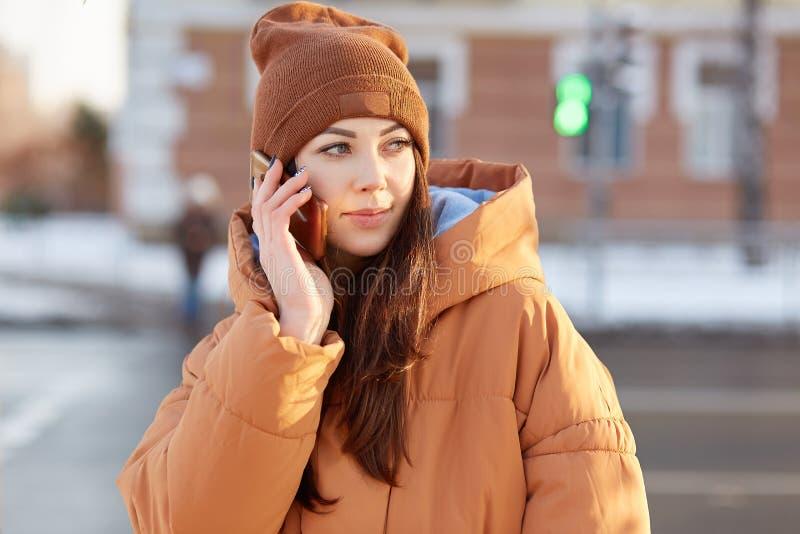 Det utomhus- skottet av den attraktiva Caucasian kvinnan rymmer mobiltelefonen, har angenäm konversation, iklädd trendig kläder,  royaltyfria bilder
