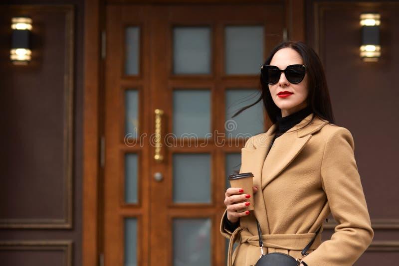 Det utomhus- skottet av den härliga unga stilfulla brunettkvinnan som bär det beigea laget som poserar i öppen luft, promenerar s arkivfoton