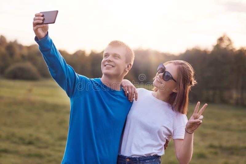 Det utomhus- skottet av glade tonåringar omfamnar och står bredvid de mot naturbakgrund, gör selfie med modern smart pho arkivbild