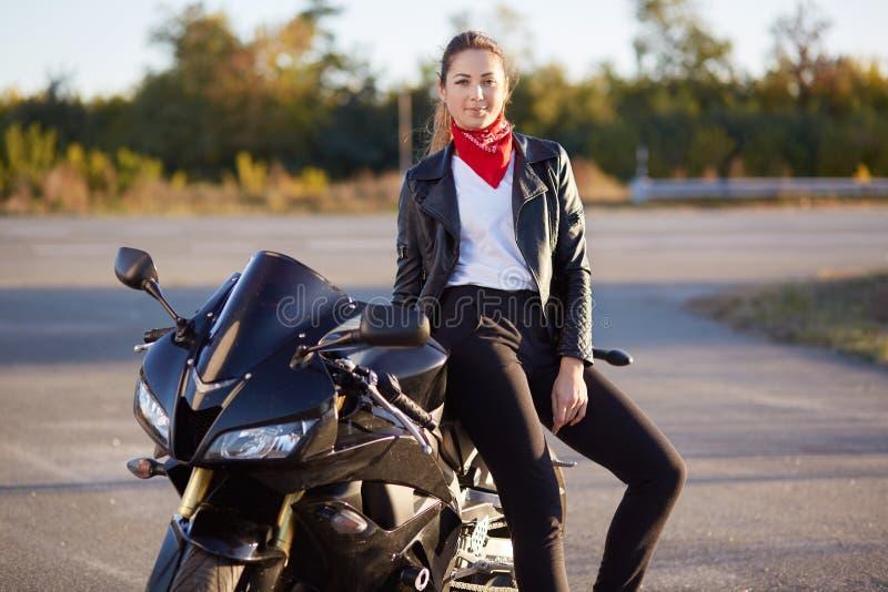 Det utomhus- skottet av kvinnan med mörkt hår som sitter på svart motobike, bär läderomslaget, byxa, den vita skjortan och den rö arkivfoton