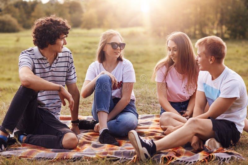 Det utomhus- skottet av lyckliga fyra vänner har gyckel tillsammans under sommarpicknicken, senast nyheterna för dicuss, delar de arkivbild