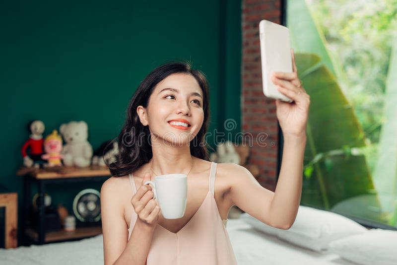 Det vård- asiatiska kvinnaleendet tar en selfie och henne sammanträde på vara arkivbilder