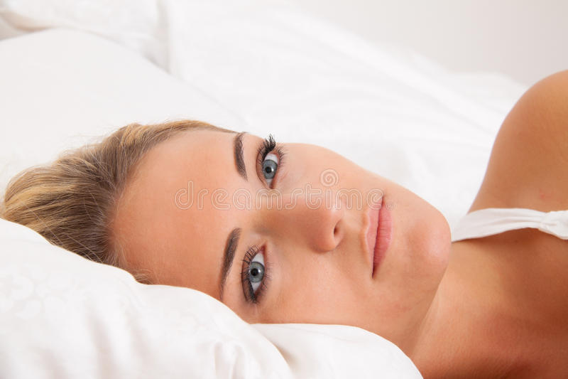 det vakna underlaget ligger den sömnlösa fundersama kvinnan royaltyfri bild