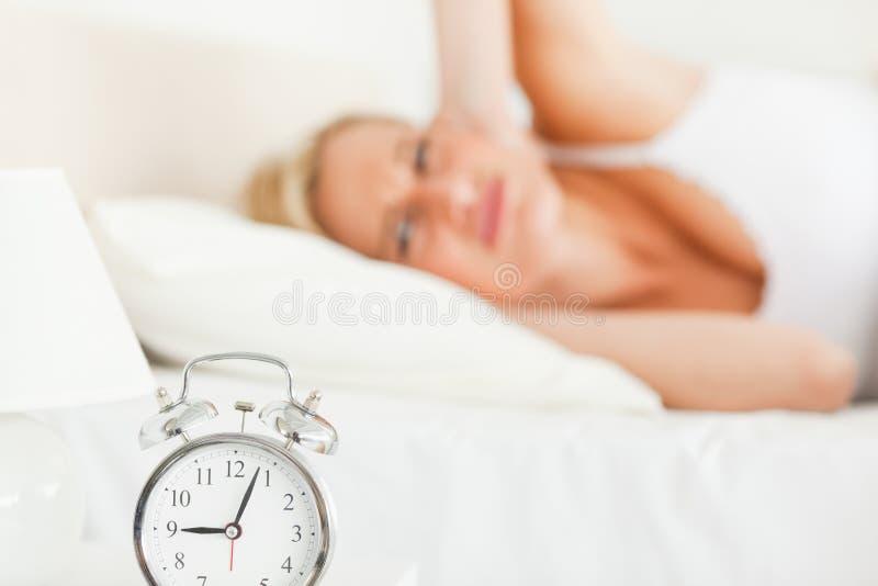 det vaknade alarmet clock henne tröttade kvinnan royaltyfria foton