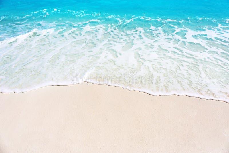Det varma sand och havet vinkar på stranden arkivfoto