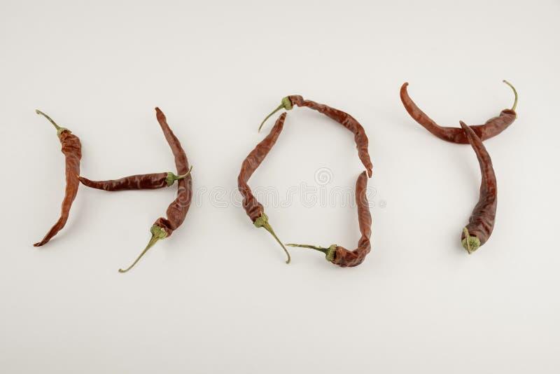 Det varmt för ord som byggs av peppar för röd chili med gröna stammar på en vit bakgrund arkivfoto