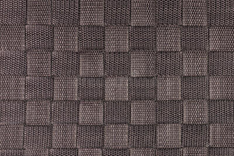 Det verkliga bruna stack tygfragmentet som gjordes av syntetiska fibrer, texturerade bakgrund, med den delikata modellen arkivbild