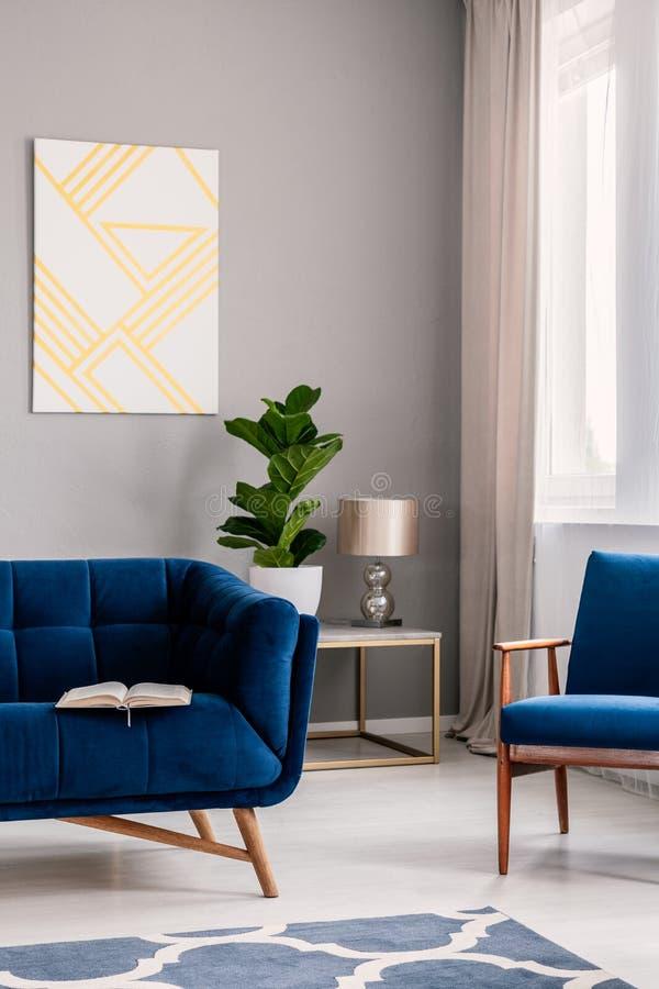 Det verkliga fotoet av ljus - grå vardagsruminre med den nya växten, fönstret med förhängear, geometrisk målning och öppnar boken royaltyfri fotografi