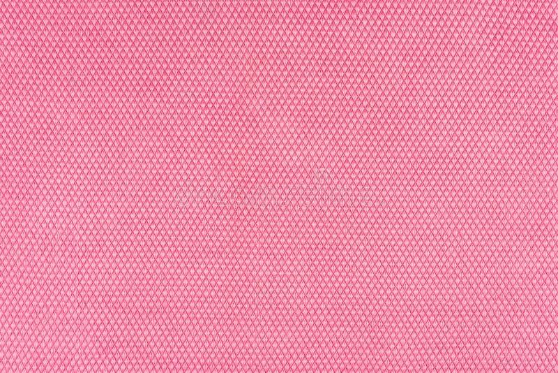 Det verkliga rosa stack tygfragmentet som gjordes av syntetiska fibrer, texturerade bakgrund, med den delikata modellen royaltyfri foto